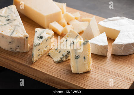 Tasting cheese dish on a wooden plate. Food for wine and romantic, cheese delicatessen on a dark stone table. - Stock Photo