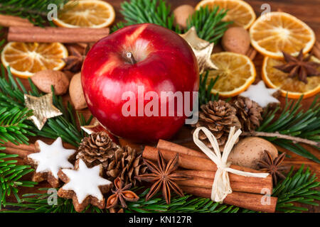 Christmas spices with Red Apple decorated over old wooden background - Stock Photo