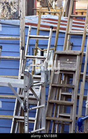a stack of different ladders and sets of steps leaning on a blue wooden shed at an old boatyard next to some scaffolding - Stock Photo