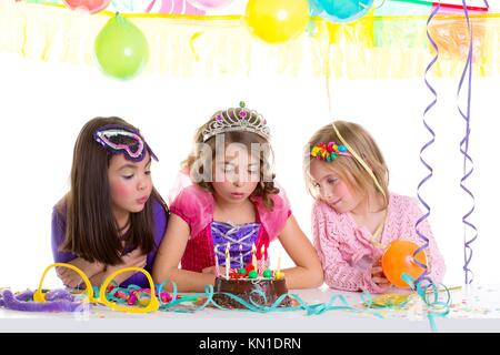 children happy girls blowing birthday party chocolate cake candles - Stock Photo