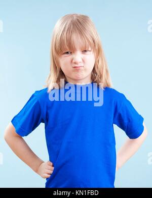 angry boy with long blond hair standing looking - isolated on blue. - Stock Photo