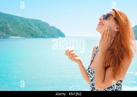 woman applying sunscreen sunblock lotion by seaside smiling happy outdoors - Stock Photo