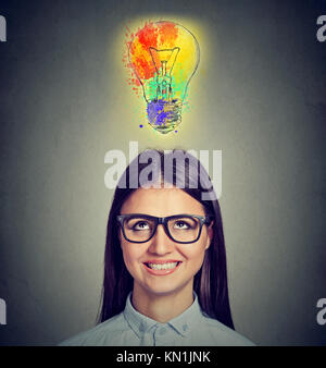 Portrait of a woman with glasses and creative idea looking up at colorful light bulb on gray background. Inspiration - Stock Photo