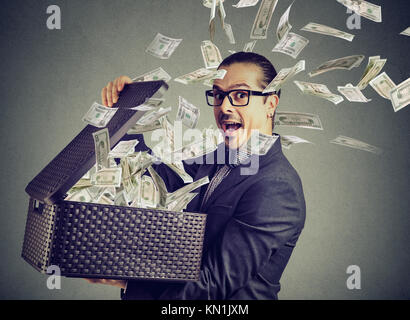 Excited successful business man opening a box with money flying out away - Stock Photo