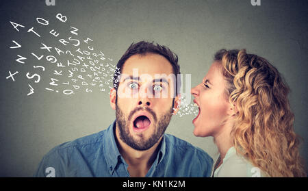 Angry woman screaming something in the ear of a shocked, scared guy isolated on gray wall background. - Stock Photo