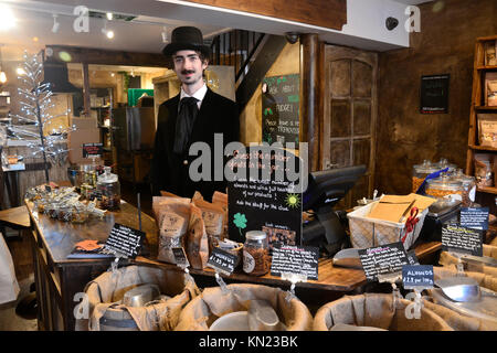 Man in Victorian dress, serving in a speciality nut shop at the Victorian Christmas Market at Stratford on Avon, - Stock Photo