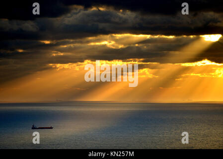 Container ship lit by rays of the setting sun, English channel. - Stock Photo