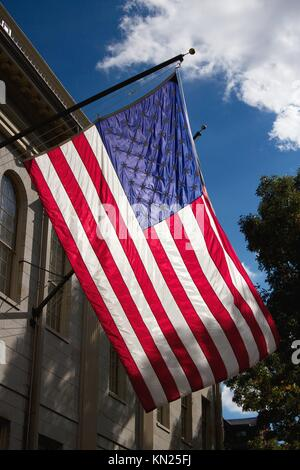 United States flag waving over the John Harvard Statue in Harvard Yard, the old heart of Harvard University campus - Stock Photo