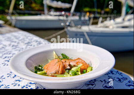A plate with salmon served in the harbor - Stock Photo