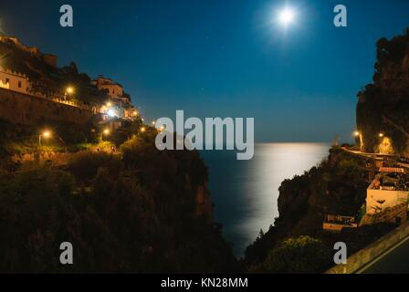 Night view of buildings and cliffs at Amalfi from a high angle, moonlight and ocean view - Stock Photo