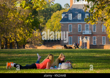 USA Virginia VA Colonial Williamsburg a couple of young women having a picnic on the Palace Green - Stock Photo