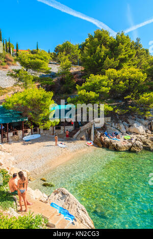 BEACH NEAR PRIMOSTEN TOWN, CROATIA - SEP 6, 2017: couple of young people relaxing at beautiful small beach near - Stock Photo