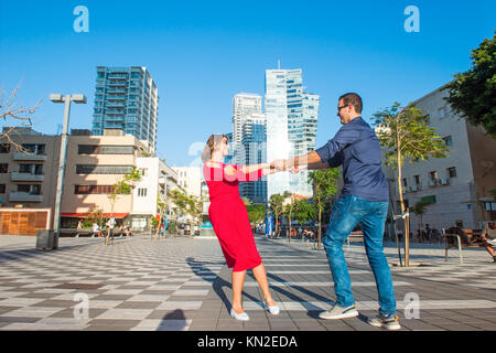 Emotional young happy couple in bright clothes and sunglasses having fun on the town Square of Tel Aviv. Smiling - Stock Photo