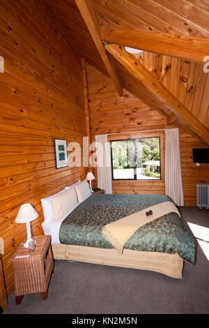 Nice warm interior of mountain wooden lodge double bedroom Fox Glacier Lodge, Fox Glacier, West Coast, South Island, - Stock Photo