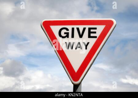 Give Way Sign against blue sky background - Stock Photo