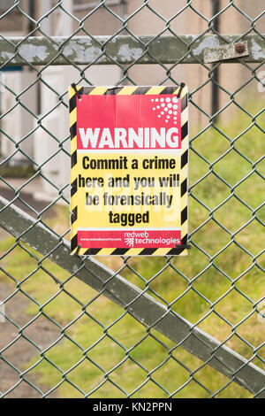 Forensic tagging warning sign on security fence - commit a crime here and you will be forensically tagged - Edinburgh, - Stock Photo