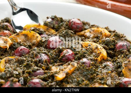 Dish with Moroccan spinach, preserved lemon and olives on white background - Stock Photo
