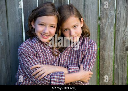 twin girls fancy dressed up pretending be siamese with his father shirt. - Stock Photo