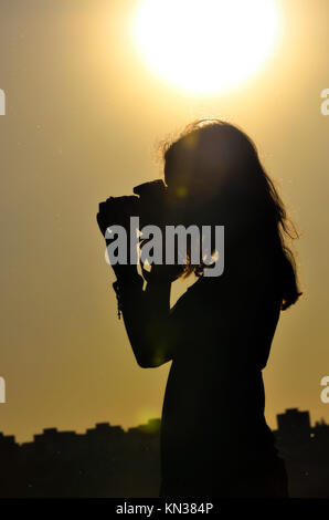 silhouette of girl isolated on sunset background in shooting time. - Stock Photo