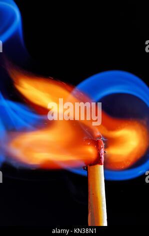 lighting a match on black background - Stock Photo