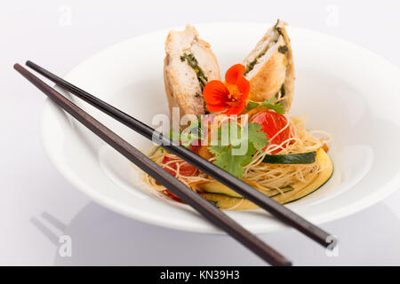 Asian food with piece of stuffed chicken, noodles, zucchini, carrots and tomatoes. - Stock Photo
