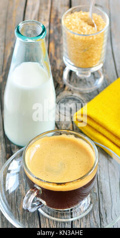 Cup of coffee with brown sugar and milk on a wooden background. - Stock Photo