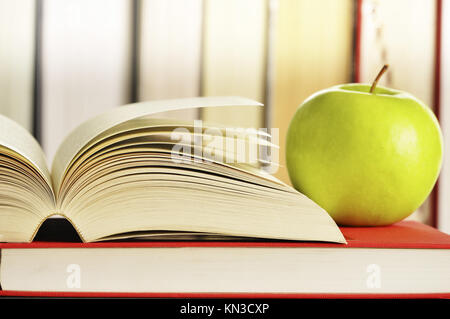 Composition with green apple and books on the table. - Stock Photo