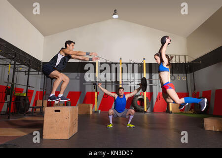 gym people group workout barbells slam balls and jump exercises. - Stock Photo