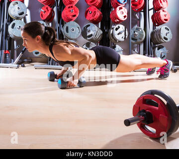 Push-ups woman with dumbbells workout fitness club at weightlifting gym. - Stock Photo
