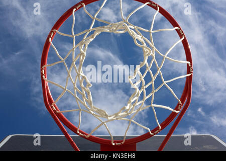 New basketball hoop from below against a cloudy sky. - Stock Photo