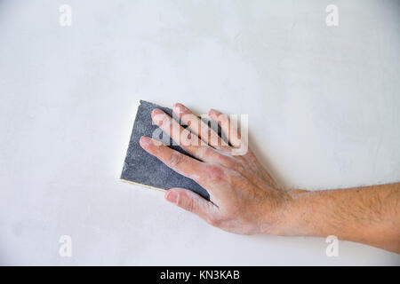 plastering man hand sanding the plaster in white wall. - Stock Photo