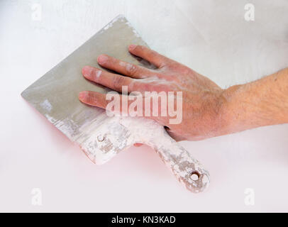 Plastering man hand with plaste and plaster spatula trowel in wall. - Stock Photo