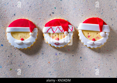 Christmas cookies with santa face in a row on recycled paper background. - Stock Photo
