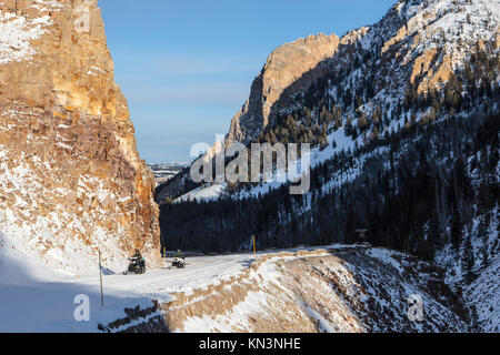 Tourists ride snowmobiles through the Golden Gate Canyon in the winter at the Yellowstone National Park January - Stock Photo