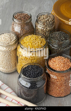 Variety of dried lentils in glass pots. - Stock Photo