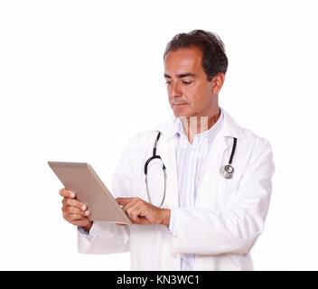 A portrait of a senior hispanic doctor using his tablet pc while standing on isolated background. - Stock Photo