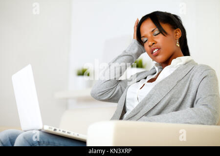 Portrait of an afro-american tired young woman with headache while is sitting on sofa at home. - Stock Photo