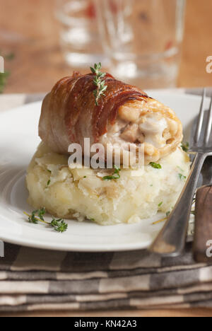 Chicken thighs wrapped in Pancetta with crushed new potatoes. - Stock Photo