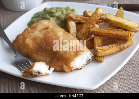 Fish and chips with crushed mushy peas on a plate. - Stock Photo