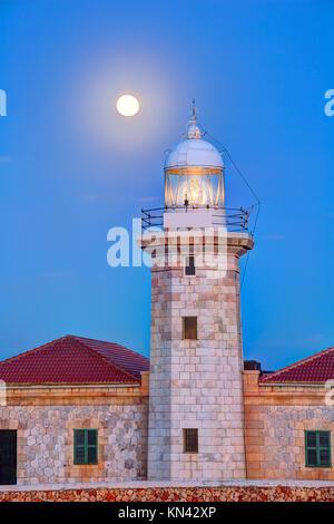 Ciutadella Menorca Punta Nati lighthouse with moon shining in sky. - Stock Photo