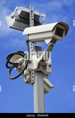 Hi-tech dome type camera over a blue sky. - Stock Photo