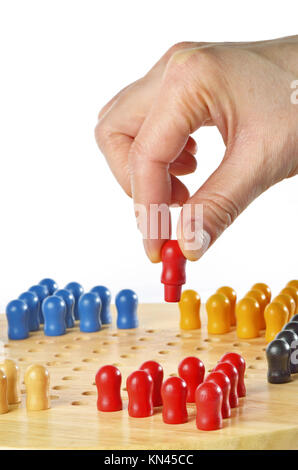 woman hand playing a game of Chinese checkers. Isolated on white. - Stock Photo