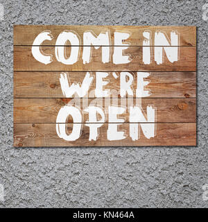 Vintage ''Come in we are open'' wooden sign on gray stucco concrete wall. - Stock Photo