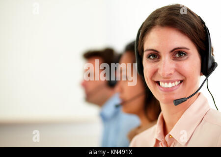 Portrait of lovely operator lady with microphone smiling at you while sitting beside her coworker on workplace  - Stock Photo