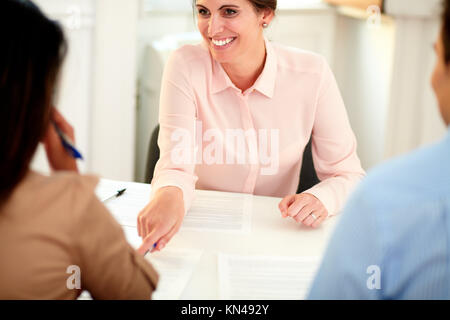 Portrait of young female bank manager working on agreement contract and explaining the application form to a young - Stock Photo