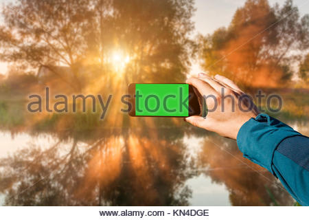 Photographing with smartphone in hand. Travel concept. Misty dawn on the river - Stock Photo