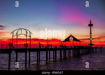 People walking along Brighton Jetty at sunset. South Australia - Stock Photo