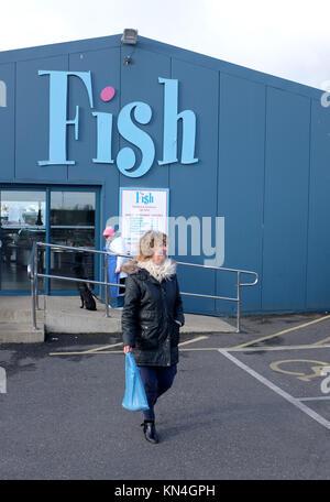 Female shopper leaving Fish the well known fresh fishmongers shop at Shoreham harbour Brighton UK - Stock Photo