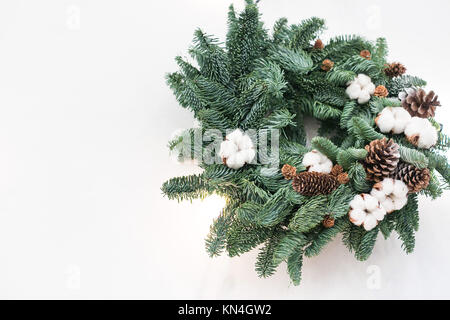 gifts of nature, traditions, christmas concept. small fuzzy wreath crafted of fresh fir branches and carefully embellished - Stock Photo