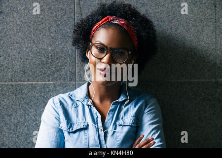 Stylishly dressed young African woman wearing glasses standing confidently with her arms crossed against a wall - Stock Photo